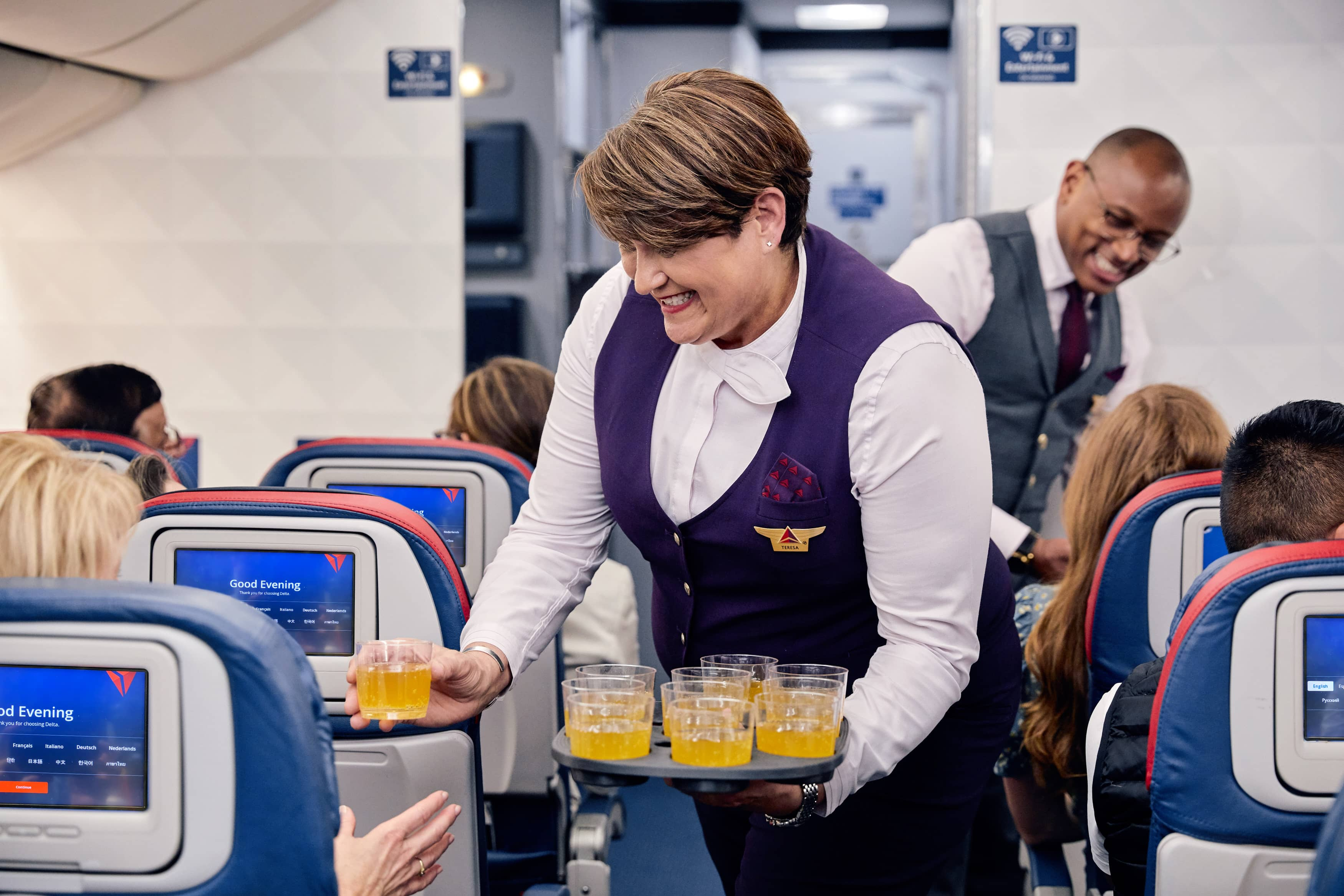 Flight stewardess serving drinks to customer on plane