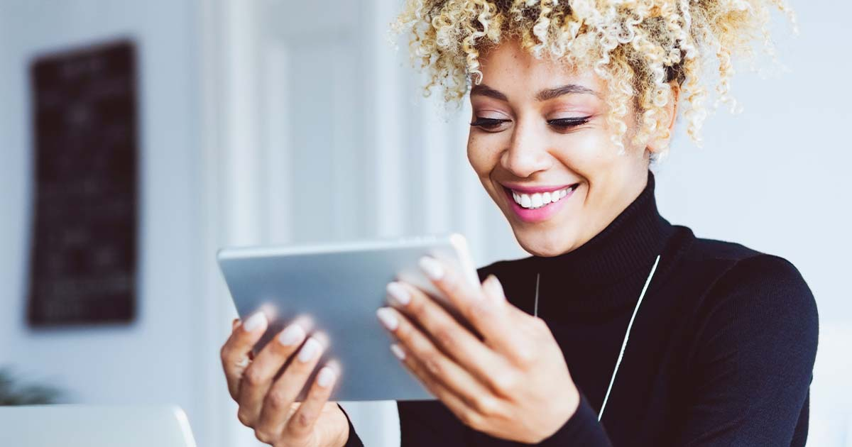 woman looking at tablet using internet