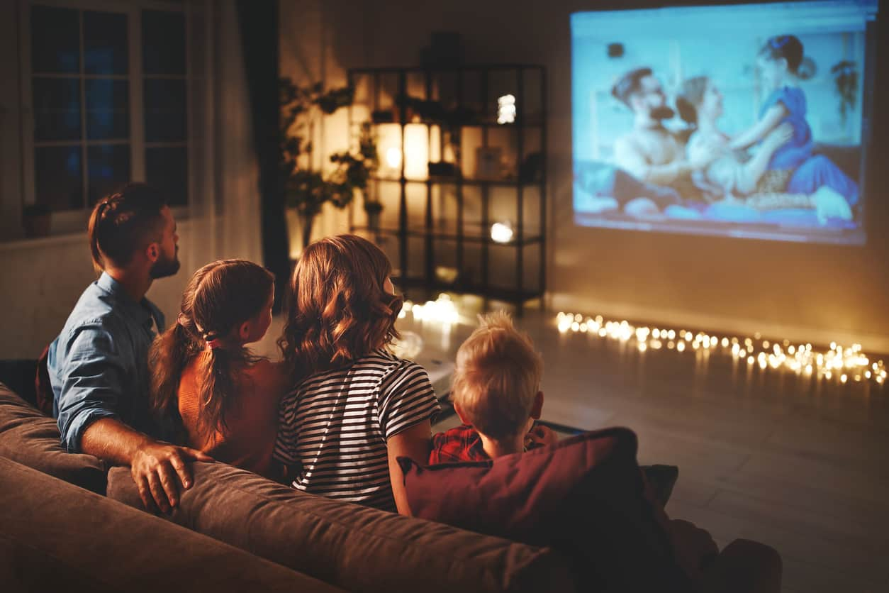 Family watching TV at night in living room | CableTV.com