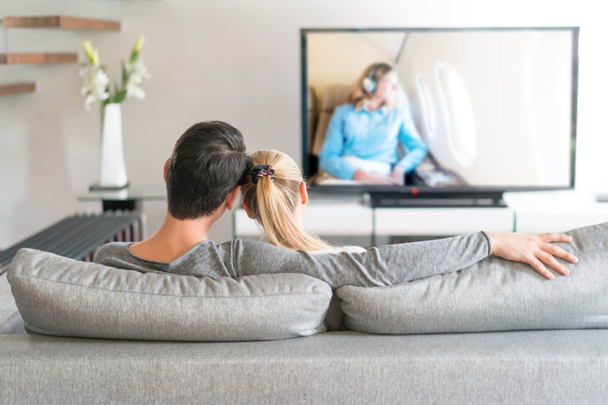 Couple sitting on a couch watching TV