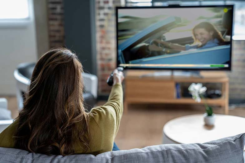 woman-pointing-remote-at-tv